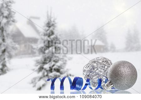 Silver Christmas decorations in the snow, snow cowered pine trees in the background