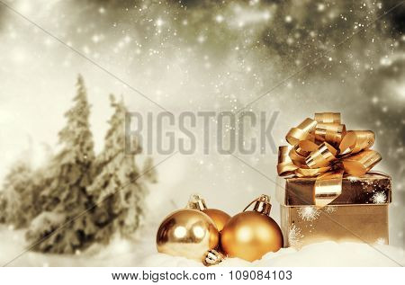 Christmas decorations and gift box in front of snow cowered pine trees