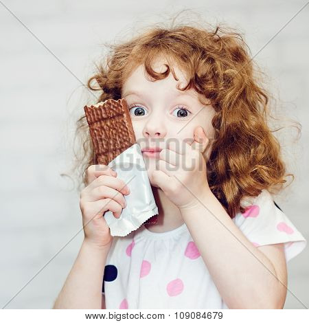 Girl With Big Blue Eyes Greedily Holding Chocolate On A Light Background.
