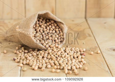 Soy Beans In Sack On Wooden Desk