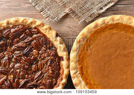 Closeup of two pies on a Thanksgiving holiday table. Pumpkin and pecan pies are traditional desserts for the American holiday.