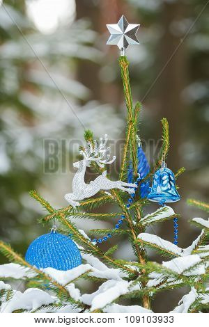 Natural spruce tree in snowy forest decorated with Christmas ornaments and star finial