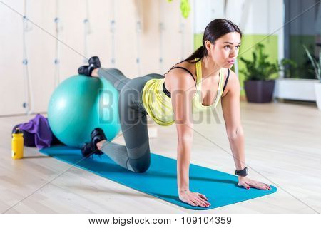 Woman doing pilates exercises with fit ball in gym or yoga class.
