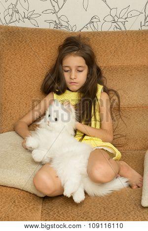 Sad little girl hugging her toy.