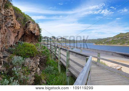 Wooden walkway and limestone wall with dune plants toward the river side beach of a river mouth in Western Australia with coastal dunes and river under a blue sky with clouds. poster