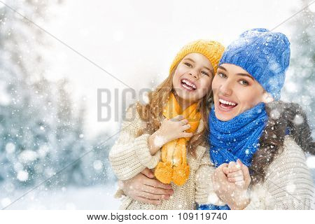 Happy family! Mother and child girl on a winter walk in nature.
