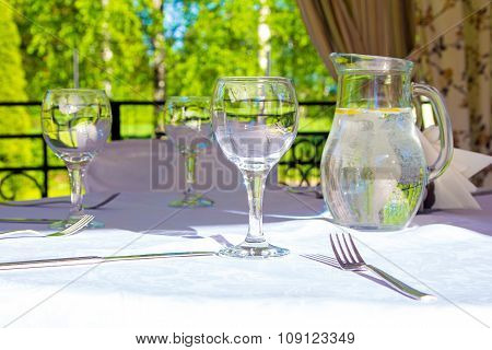 Table with glasses and white tablecloth in bower