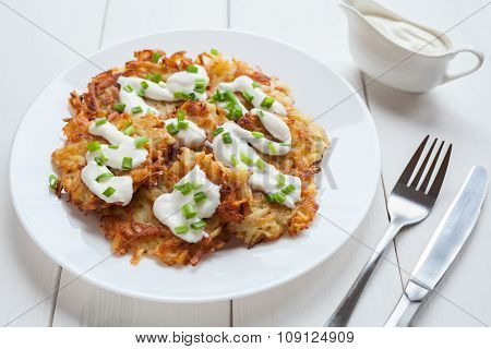 White plate of potato pancakes or latke traditional homemade vegan food with greens and sour cream o