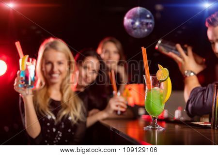 Young friends drinking cocktails together at night bar party. Focus on cocktail drink