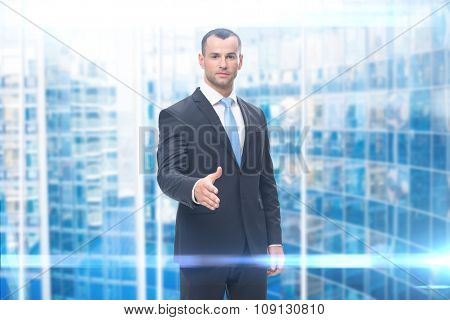 Portrait of young business man handshake gesturing, blue background. Concept of leadership and success