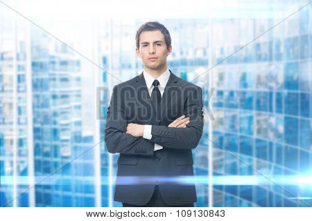 Portrait of business man with crossed hands, isolated on blue background. Concept of leadership and success