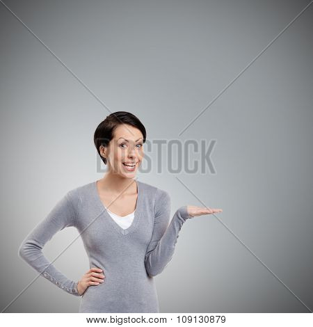 Cheerful girl gestures pointing hand, isolated on grey