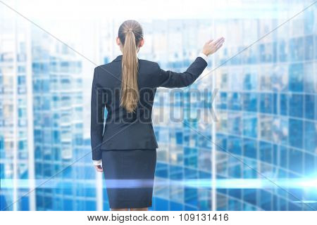 Backview of young business woman waving her hand, blue background. Concept of leadership and success