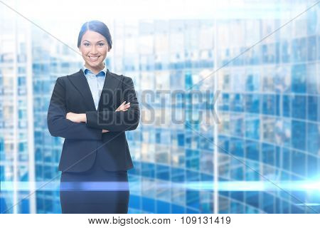 Portrait of businesswoman with hands crossed, blue background. Concept of leadership and success