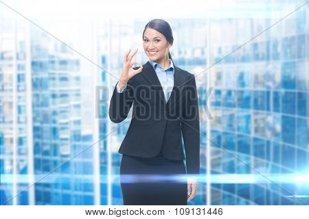 Portrait of businesswoman ok gesturing, blue background. Concept of leadership and success