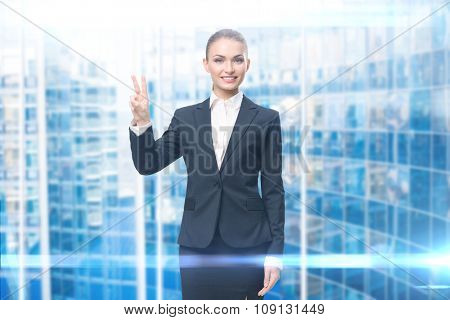 Businesswoman victory gesturing, blue background. Concept of leadership and success