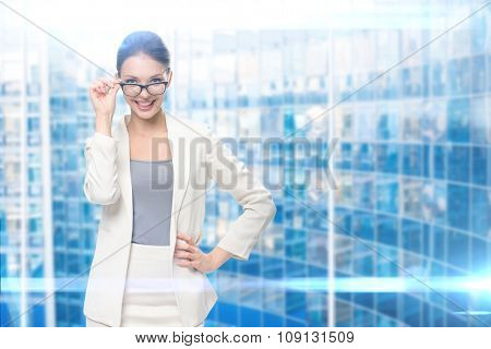 Portrait of businesswoman wearing glasses, blue background. Concept of leadership and success