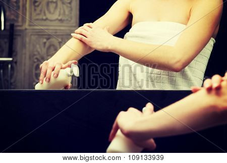 Beautiful woman with body lotion in bathroom. poster