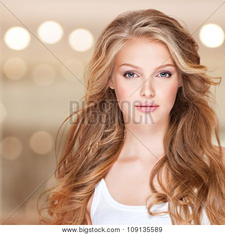 Portrait of beautiful young woman with long curly hair. Closeup face of a pretty caucasian model looking at camera