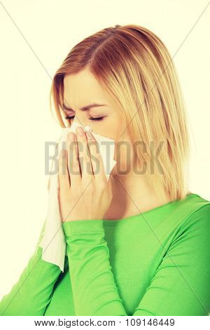 Ill woman sneezing to tissue. poster