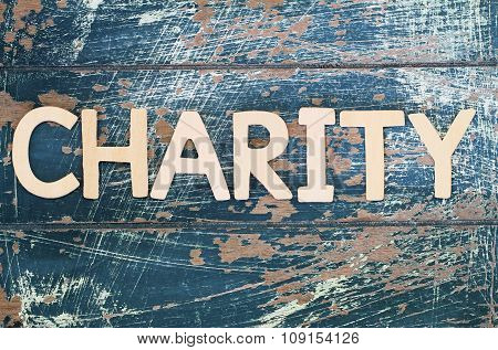 Word charity written on rustic wooden surface