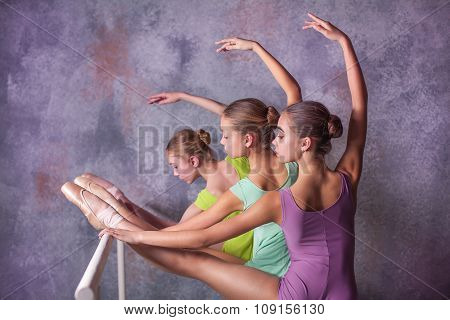 Three young ballerinas stretching on the bar