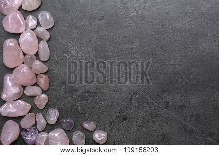 Frame of pink quartz on grey background, copy space
