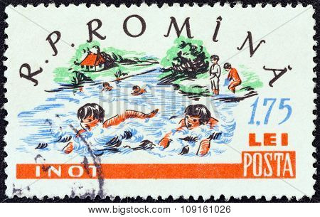 ROMANIA - CIRCA 1960: A stamp printed in Romania shows children swimming