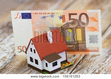 Model house in front of fifty Euro banknote on rustic wooden surface