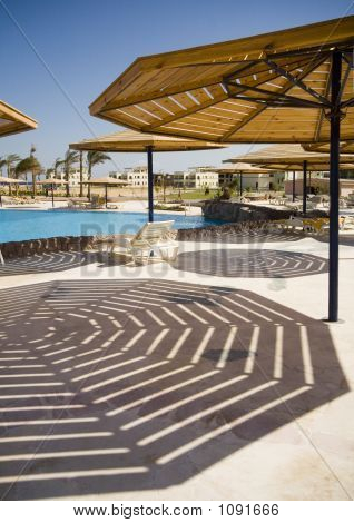 Parasol And His Striped Shadow In Hotel Near Swimming-Pool