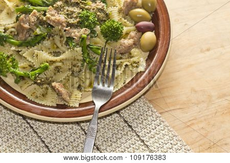 Bowtie pesto pasta with ground sausage and broccoli rabe garnished with fancy olives