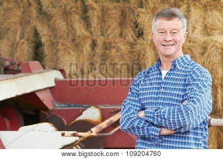 Farmer Standing In Front Of Bales And Old Farm Equipment