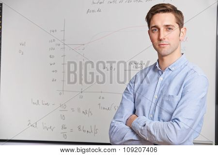 Portrait Of Teacher Standing In Front Of Whitebaord