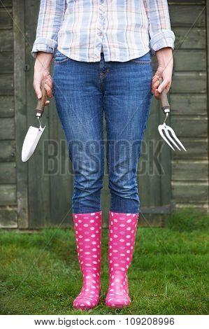 Female Gardener Holding Trowel And Fork