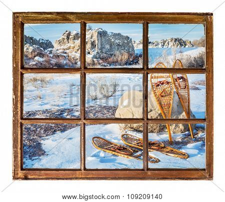 winter scene with vintage classic snowshoes as seen from a sash window of old cabin