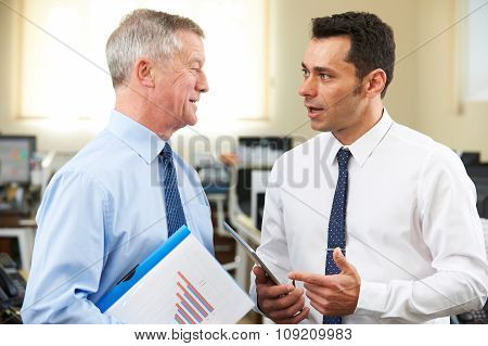 Businessman Having Discussion With Senior Mentor In Office