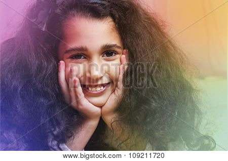 Little Cute Swarthy Brunette Girl Is On The Fur Carpet On Pink Background
