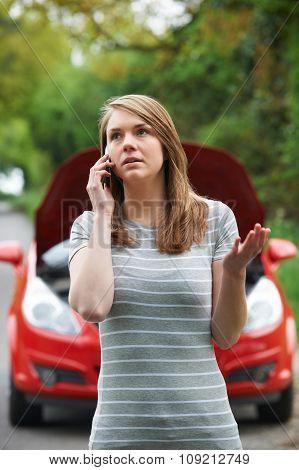 Female Motorist Phoning For Help After Breakdown