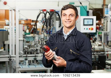 Apprentice Engineer Checking Component In Factory