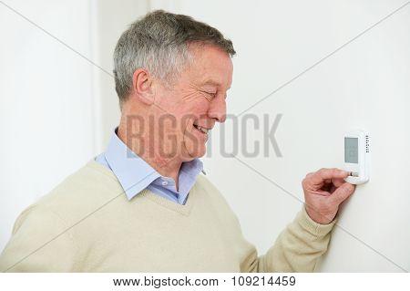 Senior Man Adjusting Central Heating Thermostat