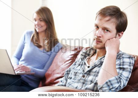 Unhappy Man Sitting On Sofa As Partner Uses Computer