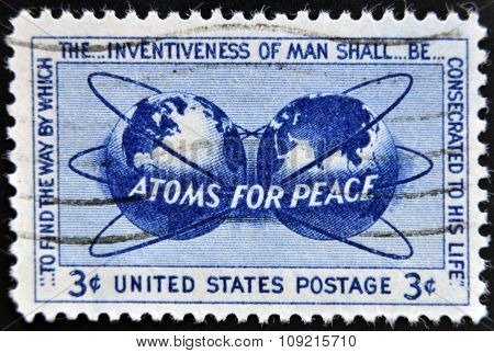 a stamp printed in USA shows Atomic Energy Encircling the Hemispheres Atoms for Peace Policy