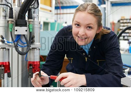 Female Apprentice Engineer Working On Machinery In Factory