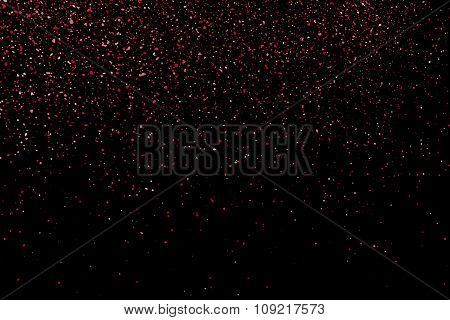 Pink glitter texture on a black background.