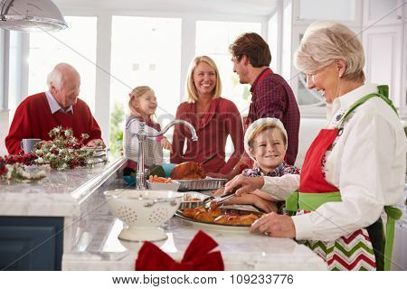 Extended Family Group Preparing Christmas Meal In Kitchen