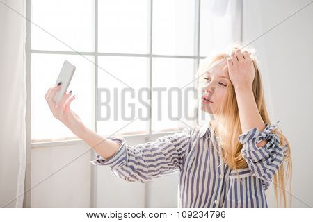Sensual young woman with blonde tousled hair takig photo of herself using mobile phone