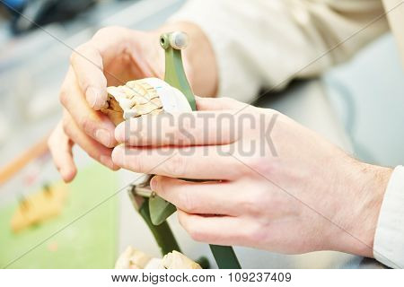 hands of male dental technician working with tooth dentures at prosthesis laboratory