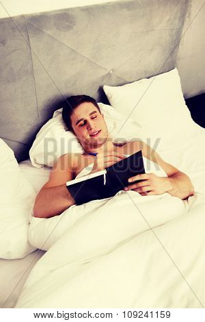 Handsome man writing a note in his bedroom on bed.