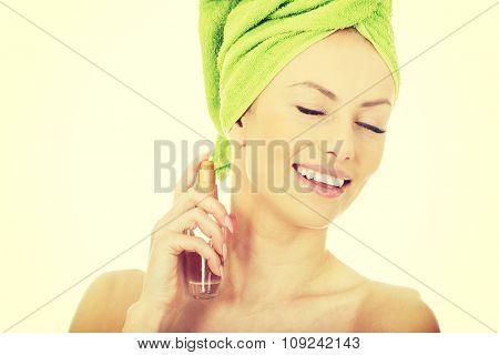 Woman in towel turban applying parfume.