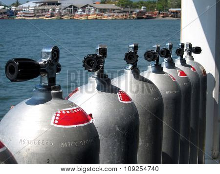 Row of scuba tanks on a dive boat at sea in Thailand.